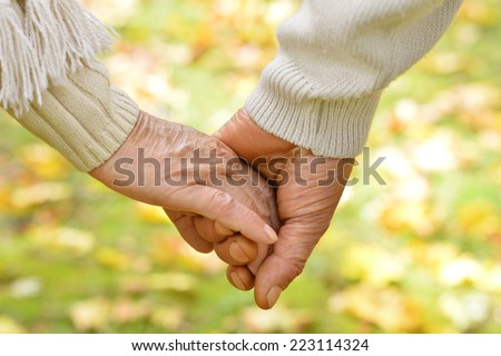 Hands held together on a natural yellow background