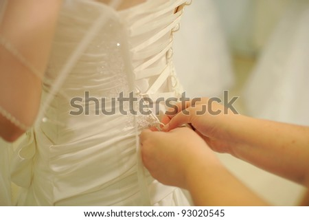 hands helping with bride's white corset - stock photo