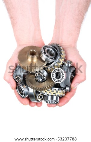 Hands hold a heap of bearings and a gear wheel on a white background