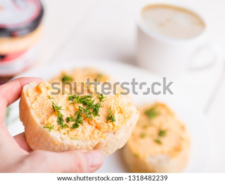 hands hold a sandwich, sandwich and cup of coffee on a light background on a served tablesandwich and cup of coffee on a light background on a served table #1318482239