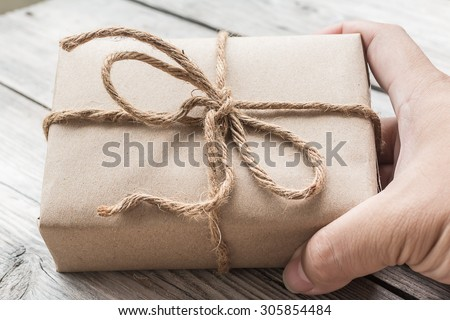Hands hold A Vintage gift box brown paper wrapped with rope on wood background