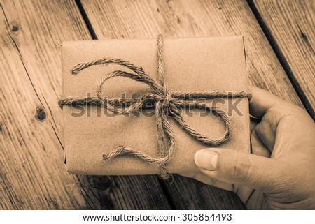 Hands hold A Vintage gift box brown paper wrapped with rope on wood background , antique tone