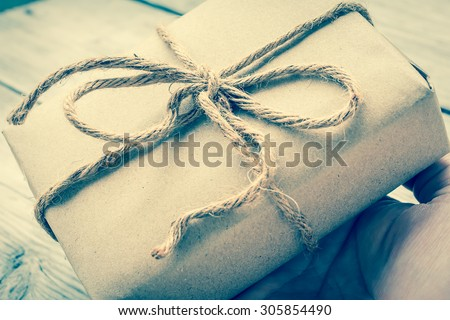 Hands hold A Vintage gift box brown paper wrapped with rope on wood background , vintage tone