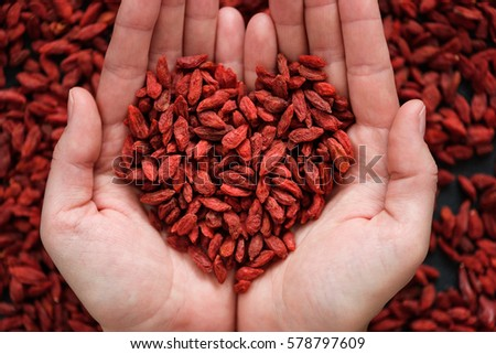 Hands hold abundance of dried goji berries top view