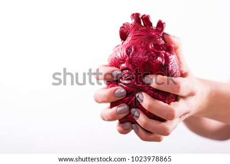 Hands hold and pump the heart on white background #1023978865