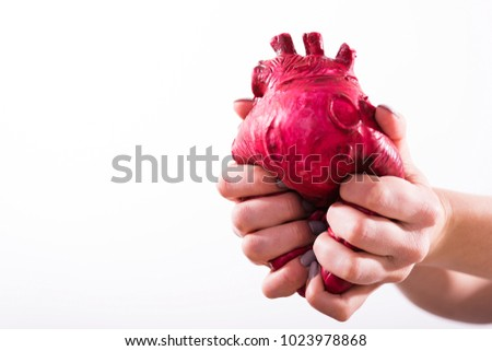 Hands hold and pump the heart on white background #1023978868