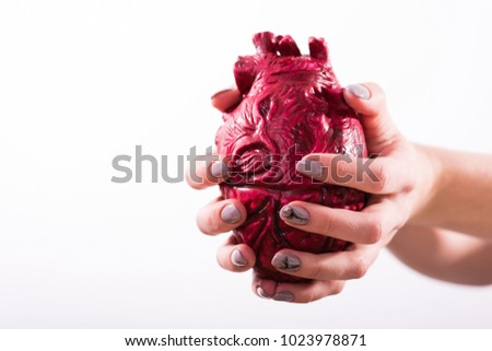 Hands hold and pump the heart on white background #1023978871