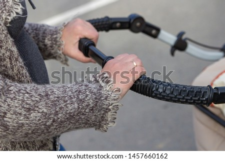hands hold baby stroller,women's hands hold a baby carriage outdoors