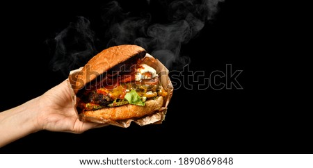 Hands hold big Burger cheeseburger sandwich with marble beef lettuce tomato cheese bacon with steam smoke on black background