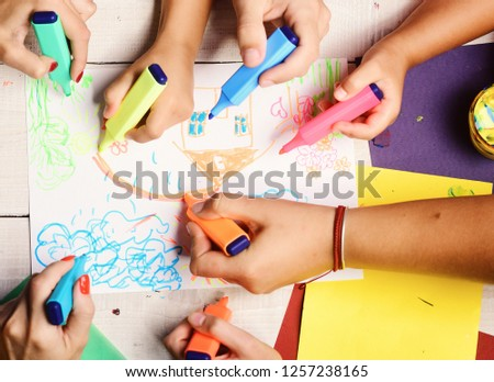 Hands hold colorful markers and draw kids illustration, top view. Artists wooden table with paints and colored paper. Markers in male and female hands draw on white paper. Creativity and art concept #1257238165