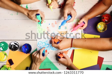 Hands hold colorful markers and draw kids illustration, top view. Markers in male and female hands draw on white paper. Art and idea concept. Artists wooden table with paints and colored paper #1263311770