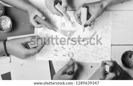 Hands hold colorful markers and draw kids illustration, top view. Markers in male and female hands draw on white paper. Artists wooden table with paints and colored paper. Art and artwork concept. #1289639347