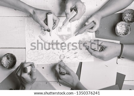 Hands hold colorful markers and draw kids illustration, top view. Markers in male and female hands draw on white paper. Artists wooden table with paints and colored paper. Art and artwork concept. #1350376241