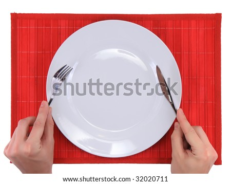 Hands hold fork and knife above  big plate on red    bamboo mat. All around Isolated. - stock photo