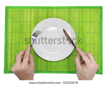 Hands hold fork and knife above  plate on green    bamboo mat. All around Isolated.