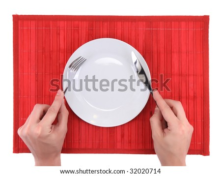 Hands hold fork and knife above   plate on yellow   bamboo mat. All around Isolated.