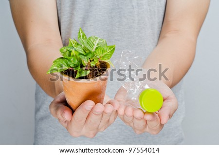 Hands hold recycle bottle and green plant, horizontal