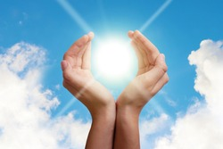 Hands hold the sun in palms on a background of blue sky with clouds. The concept of conservation of natural resources, the ozone layer. The concept of health, peace, wealth, prosperity, good luck.