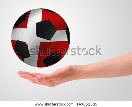Hands holding a ball with flag of denmark