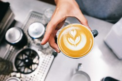 Hands holding a black cup of coffee with  a latte art heart with film look