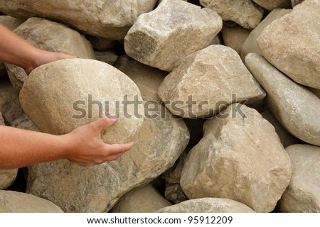 Hands holding a boulder to show scale of rocks