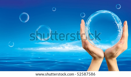 Hands holding a bubble with splashes inside against an ocean background