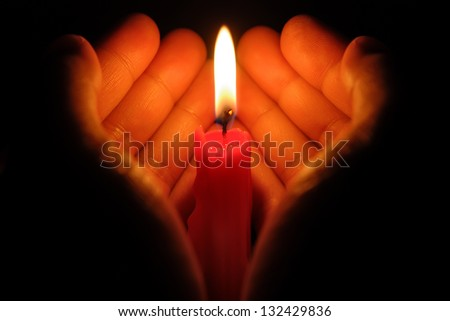 hands holding a burning candle in dark like a heart