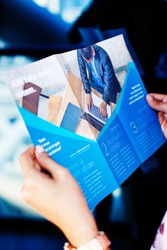 Hands holding a business brochure