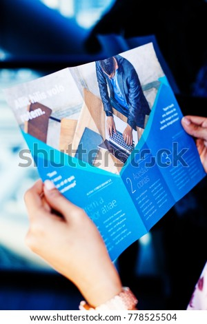 Hands holding a business brochure