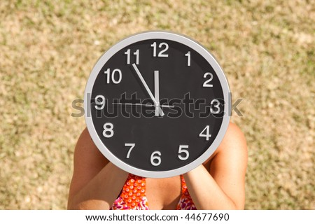 hands holding a clock in front of the face