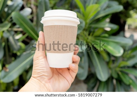 Photo of Hands holding a coffee cup that can be recycled, Coffee is one of the most popular drinks. Free space can put picture text to create an advertising media.