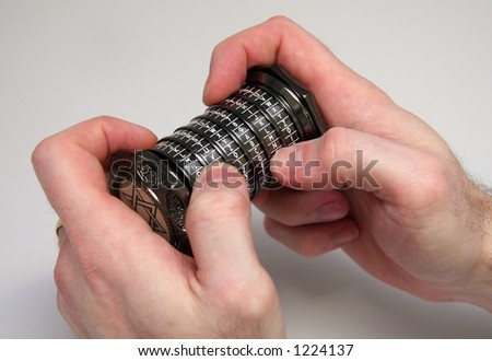 Hands holding a combination puzzle box or Cryptex - stock photo