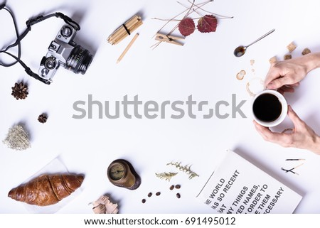 Hands holding a cup of black coffee, breakfast with croissant. Coffee break, fast snack. Top view, copy space.