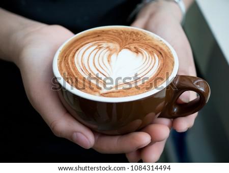 Hands holding a cup of coffee: mocha, caffe mocha  #1084314494