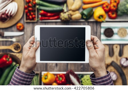 Hands holding a digital touch screen tablet, healthy vegetables and kitchen utensils on the background, nutrition and cooking concept
