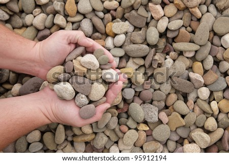 Hands holding a handful of landscaping river stone - stock photo