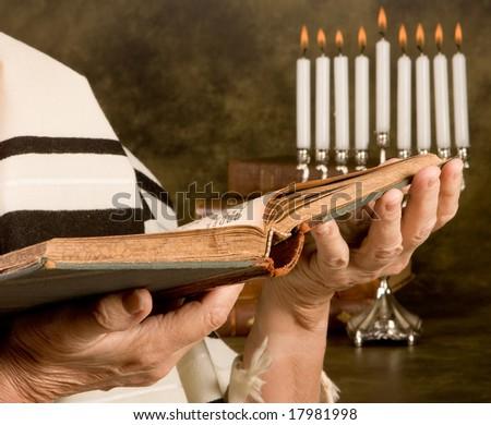Hands holding a jewish prayer book wearing a prayer shawl