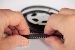 Hands holding a 8mm film strip with roll in background. Close up image with shallow depth of field.