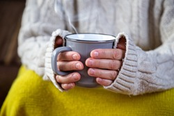 hands holding a mug with hot drink comfortably at home