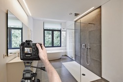Hands holding a professional camera on tripod taking picture in  tiled bathroom with windows towards garden