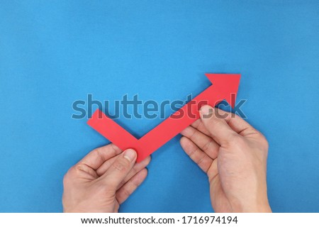 Hands holding a red arrow going up. Economy and stock market bounce back and recovery concept.  Foto d'archivio ©