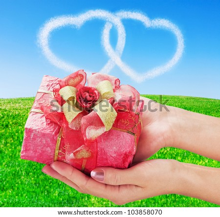 hands holding a red gifts in the sky, and two hearts