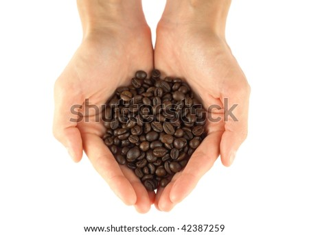 Hands holding a scoop of coffee beans