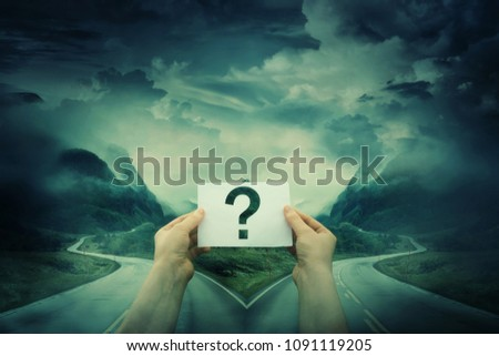 Hands holding a sheet with question mark, in front of a crossroad, fork junction where a road is splitted in two different ways. Lost people, business confusion concept, choosing the correct way.