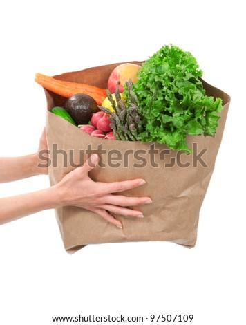 Hands holding a shopping bag full of groceries, mango, salad, asparagus, radish, avocado, lemon, carrots on white background