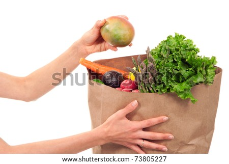Hands holding a shopping paper bag full of groceries, one hand taking out ripe mango, avocado, asparagus, carrots, radish, lime and lemon on a white background