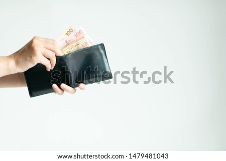 Hands holding a short wallet and one hand bring out Hong Kong money ;in currency of Dollar Hong Kong or HKD; from the wallet to pay for something on white background with copy space.