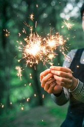 Hands holding a Sparkler in the Woods