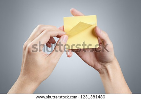 Hands holding a stack of yellow stickers on grey background #1231381480