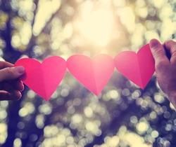 hands holding a string of paper hearts up to the sun during sunset toned with a retro vintage instagram filter effect